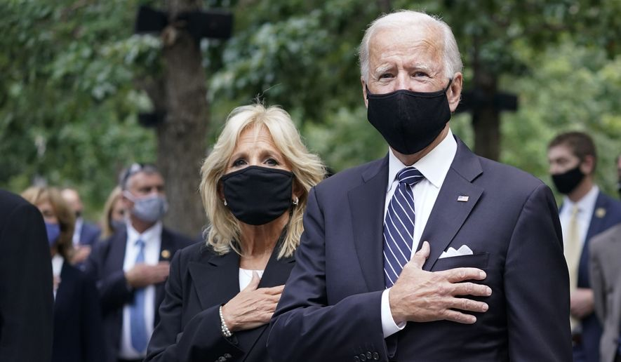 Democratic presidential candidate and former Vice President Joe Biden, right, and his wife Jill Biden stand for the pledge of allegiance during a ceremony marking the 19th anniversary of the 9/11 terrorist attacks at the National September 11 Memorial & Museum, Friday, Sept. 11, 2020, in New York. (AP Photo/Mary Altaffer)