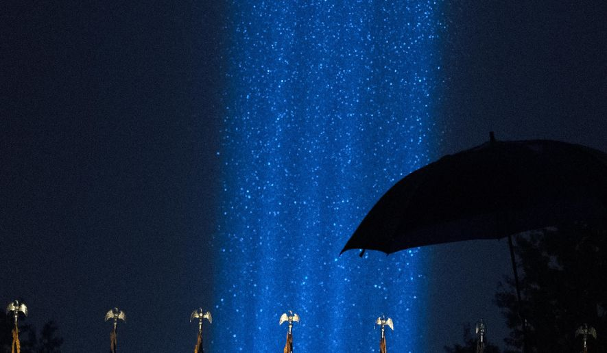 A beam of light are seen during a heavy rain over the Pentagon, as part of the Towers of Light Tribute marking the 19th anniversary of the 9/11 attack on the Pentagon, Wednesday, Sept. 9, 2020, in Washington. (AP Photo/Jose Luis Magana)