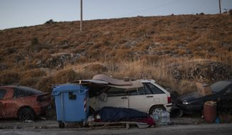 Migrants sleep on the roadside on the northeastern island of Lesbos, Greece, Friday, Sept. 11, 2020. The Greek government says thousands of migrants left homeless after fires gutted a sprawling refugee camp on the island of Lesbos will not be allowed to travel to mainland Greece. (AP Photo/Petros Giannakouris)