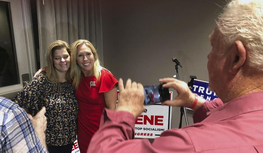 In this Tuesday, Aug. 11, 2020 file photo, Supporters take photos with construction executive Marjorie Taylor Greene, background right, late in Rome, Ga. The Democratic candidate running against Republican Marjorie Taylor Greene, who has expressed support for the QAnon conspiracy theory and been criticized for other incendiary comments, is dropping out of their race for a U.S. House seat representing northwest Georgia. Democrat Kevin Van Ausdal bowed out of the race on Friday, Sept. 11, 2020.  (AP Photo/Mike Stewart, File)