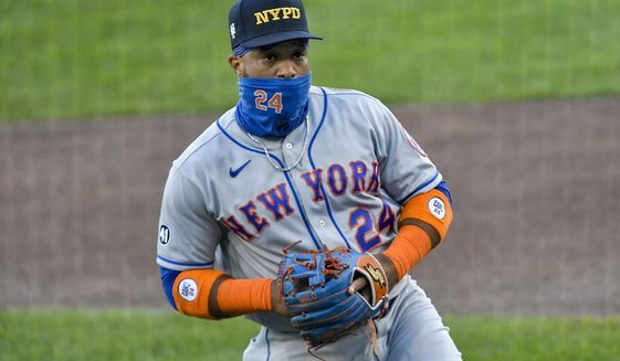 New York Mets second baseman Robinson Cano wears a New York Police Department cap while warming up before a baseball game against the Toronto Blue Jays in Buffalo, N.Y., Friday, Sept. 11, 2020. Mets players and coaches wore first responder caps in honor of the 19th anniversary of the Sept. 11, 2001, terror attacks. (AP Photo/Adrian Kraus)