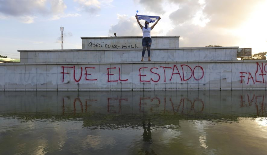 """FILE - In this June 1, 2018 file photo, a masked protestor holds up a Nicaraguan flag above the Spanish graffiti phrase: """"The state did it,"""" during a protest against the government of President Daniel Ortega on National Children's Day in Managua, Nicaragua. Nineteen Nicaraguans who say they suffered torture and sexual abuse at the hands of their country's security forces during anti-government protests from April to August 2018 testified in San Jose, Costa Rica to a panel of legal and psychological experts the week of Sept. 11, 2020. (AP Photo/Alfredo Zuniga, File)"""