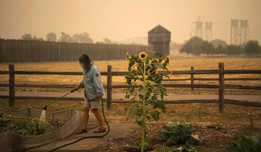 "Volunteer Elizabeth Stoltz of Heisson waters the Fort Vancouver Garden in Vancouver, Wash., Friday, Sept. 11, 2020. Stolz said things were extra dried out because of the wind and smoke. ""The wind sucks the life out of everything,"" she said. Stoltz said she is still not under evacuation from the Big Hollow Fire but her family made a plan in case it gets to that point. Clark County entered hazardous air-quality territory late Thursday as wildfire smoke traveling from other areas enveloped Southwest Washington. (Alisha Jucevic/The Columbian via AP)"