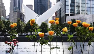 Flowers are placed in the inscribed names of the deceased at the National September 11 Memorial and Museum, Friday, Sept. 11, 2020, in New York. (AP Photo/John Minchillo)