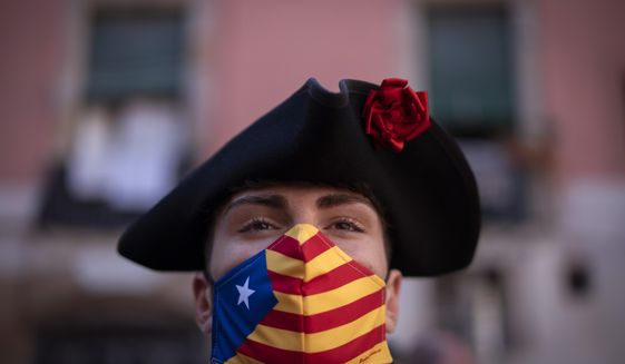 """A man wearing a face mask decorated with the independent flag looks on during the Catalan National Day in Barcelona, Spain, Friday, Sept. 11, 2020. Thousands of Catalans in favour of gaining independence from the rest of Spain are expected to rally Friday afternoon in commemoration of """"La Diada"""", Catalan for the region's """"national"""" day. Dozens of distance-minded protests in different parts of the region are meant to create, according to organizers, the largest demonstration in Europe in times of COVID-19. (AP Photo/Emilio Morenatti)"""