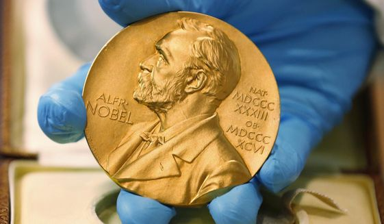 FILE- In this file photo dated Friday, April 17, 2015, a national library employee shows the gold Nobel Prize medal awarded to the late novelist Gabriel Garcia Marquez, in Bogota, Colombia.  Swedish lawmaker Magnus Jacobsson tweeted Friday Sept. 11, 2020, that he has nominated the governments of the United States, Kosovo and Serbia for the Nobel Peace Prize, for their efforts to secure a peace agreement between the two former Balkan war foes. (AP Photo/Fernando Vergara, FILE)