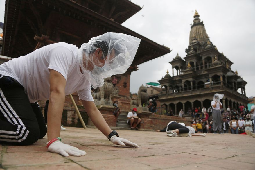 FILE - In this June 30, 2020, file photo, Nepalese youth perform a play as part of a protest demanding better COVID-19 management at Patan Durbar Square near Kathmandu, Nepal. (AP Photo/Niranjan Shrestha, File)