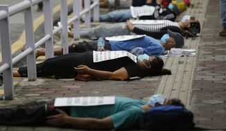 FILE - In this June 20, 2020, file photo, protesters lie on the ground demanding better handling of the COVID-19 pandemic in Kathmandu, Nepal. (AP Photo/Niranjan Shrestha, File)