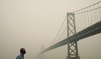 Smoke and haze from wildfires partially obscures the view of the San Francisco-Oakland Bay Bridge along the Embarcadero in San Francisco, Thursday, Sept. 10, 2020. (AP Photo/Jeff Chiu)