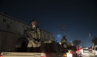 In this Nov. 28, 2019, file photo armed soldiers stand guard in the motorcade for President Donald Trump speaks during a surprise Thanksgiving Day visit to the troops at Bagram Air Field, Afghanistan. (AP Photo/Alex Brandon, File)  **FILE**