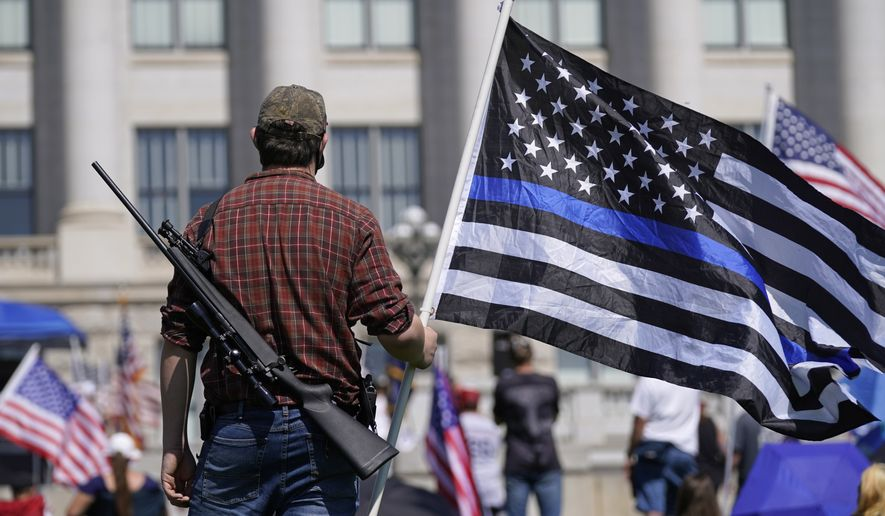 Jacob Dolenc holds a blue lives matter flag while showing his support during a Unity Rally at the Utah State Capitol Saturday, Sept. 12, 2020, in Salt Lake City. (AP Photo/Rick Bowmer)