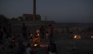 Refugees and migrants cook on makeshift fires near an abandoned factory in the island of Lesbos, Greece, Friday, Sept. 11, 2020.  Some thousands of refugees and migrants have spent a third night in the open on the Greek island of Lesbos after two consecutive nights of fires in the notoriously overcrowded Moria camp left them homeless. (AP Photo/Petros Giannakouris)
