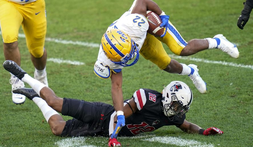 Pittsburgh running back Vincent Davis (22) tries to avoide Austin Peay cornerback Nathan Page (12) on a run during the second half of an NCAA college football game Saturday, Sept. 12, 2020, in Pittsburgh. (AP Photo/Keith Srakocic)