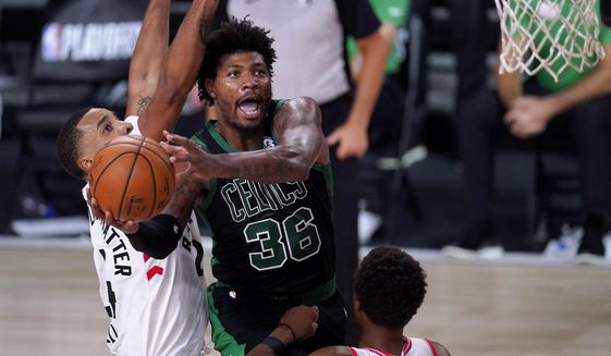 Boston Celtics' Marcus Smart (36) goes up for a shot against Toronto Raptors' Norman Powell, left, and Kyle Lowry during the second half of an NBA conference semifinal playoff basketball game Friday, Sept. 11, 2020, in Lake Buena Vista, Fla. (AP Photo/Mark J. Terrill)