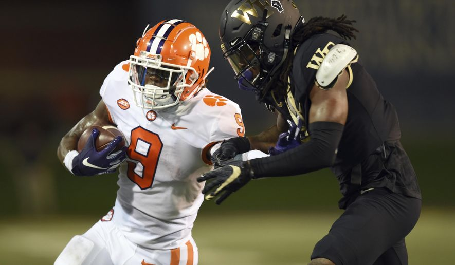 Clemson running back Travis Etienne, left, is taken down by Wake Forest's Ja'Sir Taylor after a long run in the first half of an NCAA college football game Saturday, Sept. 12, 2020, in Winston-Salem, N.C. (Walt Unks/The Winston-Salem Journal via AP)