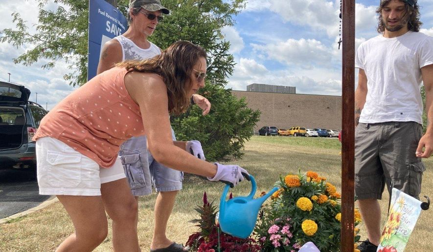 Dave Baird, left, watches as his wife, Jennifer Baird, waters flowers on Saturday, Aug. 29, 2020, at a memorial where their son, Charlie, was fatally shot on May 11 in New Lenox, Ill. Charlie Baird's friend, Nathan McAvoy, 19, right, made the wooden cross that anchors the display at a Circle K gas station (Ted Slowik/Southtown Star via AP)