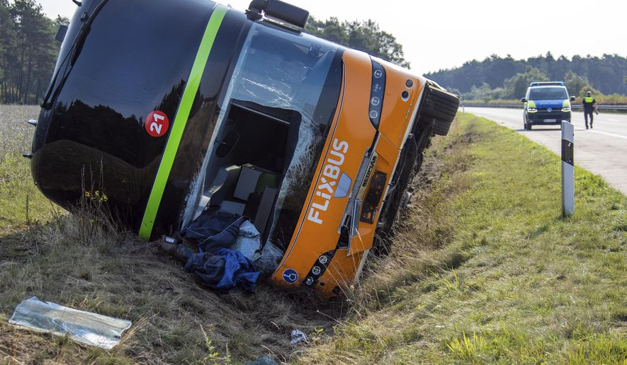 A a long-distance bus lies in the ditch along the A24 motorway in Woebbelin, northern Germany, Saturday, Sept. 12, 2020. According to police several people were injured in a long-distance bus accident early Saturday morning. (Jens Buettner/dpa via AP)