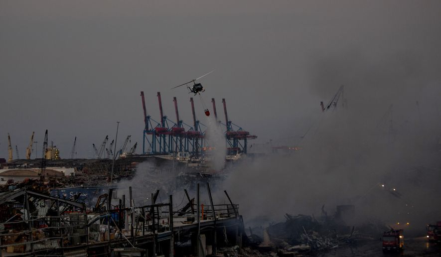 An army helicopter drops water on a fire at warehouses at the seaport in Beirut, Lebanon, Friday, Sept. 11, 2020. A huge fire has broken out Yesterday at the Port of Beirut, sending up a thick column of black smoke and raising new panic among traumatized residents after last month's catastrophic blast at the same site. (AP Photo/Hassan Ammar)