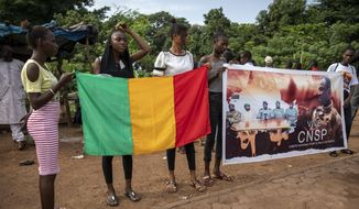 People hold a banner showing Col. Assimi Goita, leader of the junta which is now running Mali and calls itself the National Committee for the Salvation of the People, outside a conference in Bamako, Mali, Thursday, Sept. 10, 2020. Leaders of Mali's military junta who deposed the West African country's president last month are meeting with political parties and civil society groups to outline a transition to a civilian government and, ultimately, elections. (AP Photo)