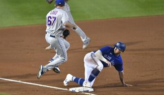 New York Mets starting pitcher Seth Lugo, left, jumps off the base after forcing out Toronto Blue Jays' Travis Shaw at third during the fourth inning of a baseball game in Buffalo, N.Y., Saturday, Sept. 12, 2020. The call was upheld after a Toronto challenge. (AP Photo/Adrian Kraus)