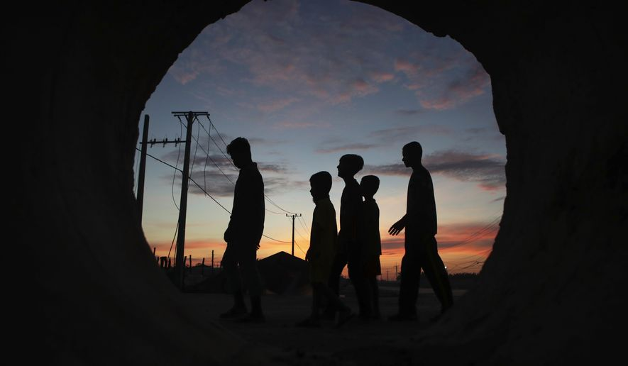 Seen through a large pipe, a group of boys walk together after they offered food at a Buddhist pagoda during the Pchum Ben festival (Ancestors' Day) in the village of Kob Srov, on the outskirts of Phnom Penh, Cambodia, early Sunday morning, Sept. 6, 2020. The traditional 15-day holiday pays respects to deceased relatives. (AP Photo/Heng Sinith)