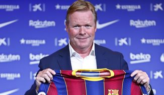 Ronald Koeman holds up a Barcelona soccer shirt during his official presentation as coach for FC Barcelona in Barcelona, Spain, Wednesday, Aug. 19, 2020. Barcelona officially announced earlier on Wednesday a deal with Koeman to become their coach five days after the team's humiliating 8-2 loss to Bayern Munich in the Champions League quarterfinals. Barcelona says the former defender's deal runs through June 2022. Koeman replaces the fired Quique Setien. (AP Photo/Joan Monfort)
