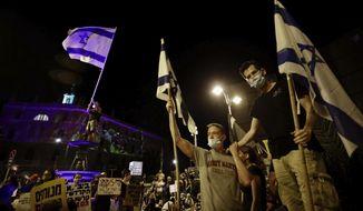 Israeli protesters wave flags during a demonstration against Israeli Prime Minister Benjamin Netanyahu outside the Prime Minister's residence in Jerusalem, Saturday, Sept. 12, 2020. (AP Photo/Sebastian Scheiner)