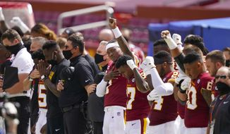 Washington Football Team quarterback Dwayne Haskins (7) and others hold their fist in the air during the national anthem before the start of an NFL football game against the Philadelphia Eagles, Sunday, Sept. 13, 2020, in Landover, Md. (AP Photo/Alex Brandon)  **FILE**
