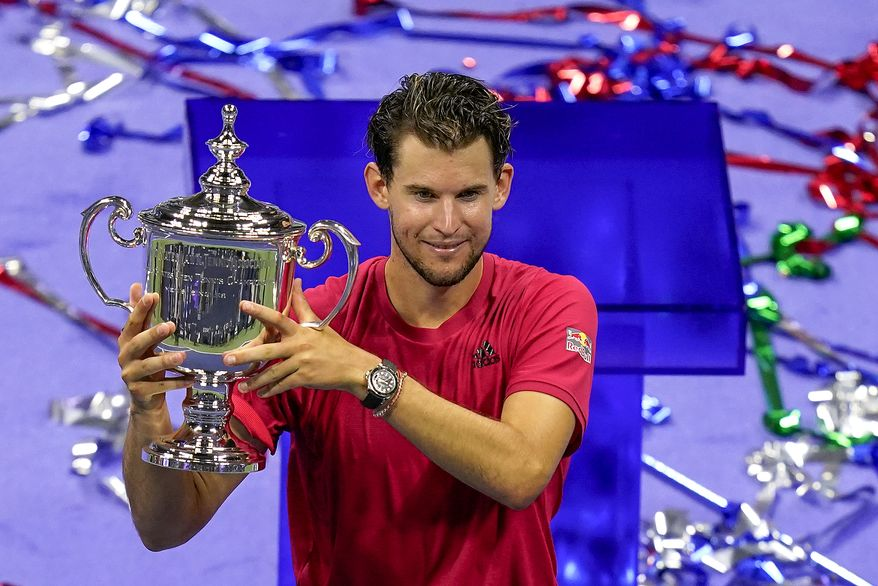 Dominic Thiem, of Austria, holds up the championship trophy after defeating Alexander Zverev, of Germany, in the men's singles final of the US Open tennis championships, Sunday, Sept. 13, 2020, in New York. (AP Photo/Seth Wenig)