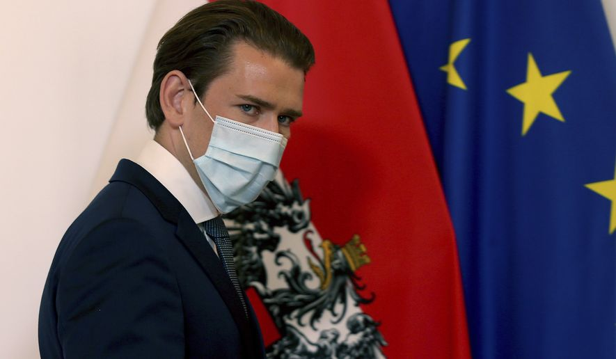 Austrian Chancellor Sebastian Kurz walks wearing a face mask, at the federal chancellery in Vienna, Austria, Sunday, Sept. 13, 2020. The Austrian government has moved to restrict freedom of movement for people, in an effort to slow the onset of the COVID-19 coronavirus. (AP Photo/Ronald Zak)