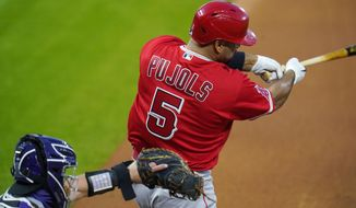 Los Angeles Angels' Albert Pujols, right, connects for a single as Colorado Rockies catcher Tony Wolters looks for the pitch in the fourth inning of a baseball game Saturday, Sept. 12, 2020, in Denver. (AP Photo/David Zalubowski)