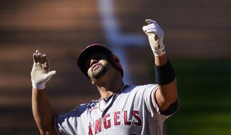 Los Angeles Angels' Albert Pujols gestures as he crosses home plate after hitting a two-run home run in the eighth inning of a baseball game Sunday, Sept. 13, 2020, in Denver. (AP Photo/David Zalubowski)