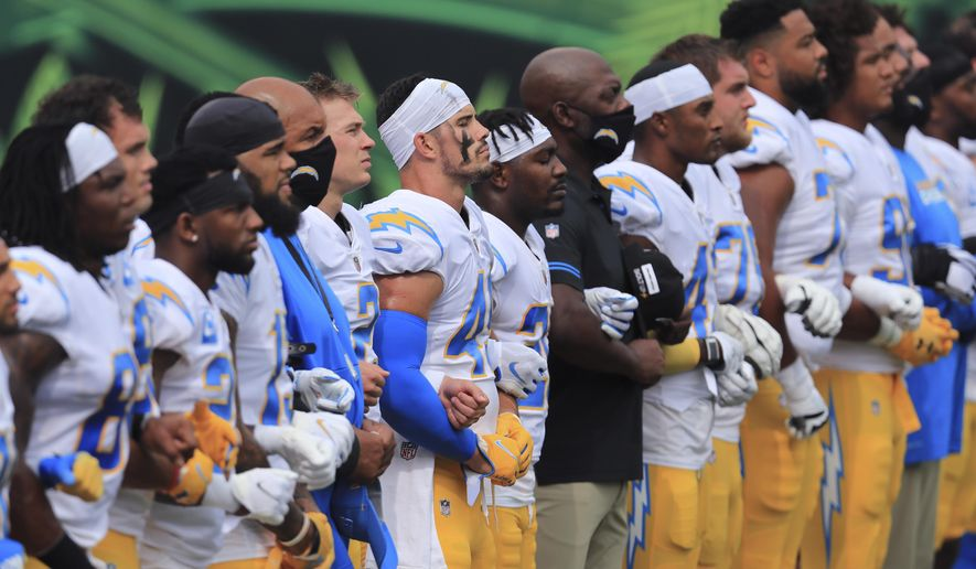 """The Los Angeles Chargers stand arm-in-arm as """"Lift Every Voice and Sing"""" is played before an NFL football game against the Cincinnati Bengals, Sunday, Sept. 13, 2020, in Cincinnati. (AP Photo/Aaron Doster)"""