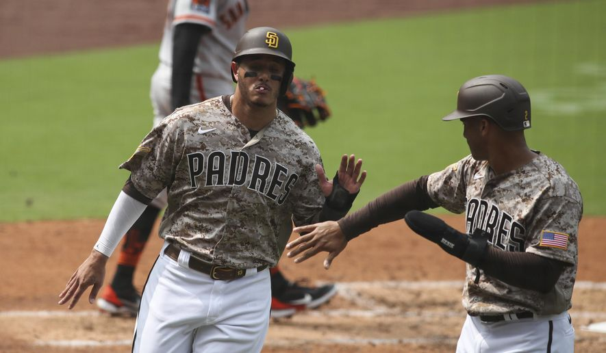 San Diego Padres third baseman Manny Machado high fives Trent Grisham after they score on a single to left field hit by Will Myers against the San Francisco Giants in the third inning of a baseball game Sunday, Sept. 13, 2020, in San Diego. (AP Photo/Derrick Tuskan)