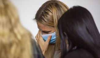 Israeli top model Bar Refaeli wears a face mask amid the coronavirus pandemic as she speaks to her lawyers inside a courtroom in Tel Aviv, Israel, Sunday, Sept. 13, 2020. The Israeli court sentenced top model Bar Refaeli to nine months of community service and her mother was sentenced to 16 months in prison, ending a prolonged tax evasion case that had sullied the image of a once beloved national icon. (AP Photo/Ariel Schalit, Pool)