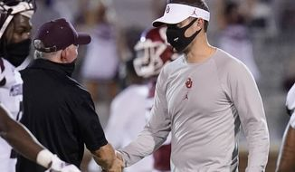 Missouri State coach Bobby Petrino, left, and Oklahoma coach Lincoln Riley shake hands after an NCAA college football game Saturday, Sept. 12, 2020, in Norman, Okla. (AP Photo/Sue Ogrocki, Pool)