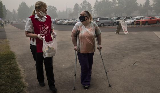 Mary Thomson, left, from Phoenix gets assistance from Salvation Army officer Tawnya Stumpf at the evacuation center set up at the Jackson County Fairgrounds on Saturday, Sept. 12, 2020 in Central Point, Ore. They lost their home to the destructive wildfires devastating the region. (AP Photo/Paula Bronstein)