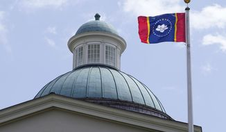 """The magnolia flower centered banner chosen Wednesday, Sept. 2, 2020 by the Mississippi State Flag Commission flies outside the Old State Capitol Museum in downtown Jackson, Miss. The nine member committee voted to recommend a design with the state flower, now known as the """"In God We Trust,"""" flag. That design will go on the November ballot for voters consideration and if approved, it will become the new state flag. (AP Photo/Rogelio V. Solis)"""