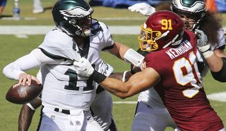 Washington Football Team defensive end Ryan Kerrigan (91) takes down Philadelphia Eagles quarterback Carson Wentz (11) for a sack during an NFL match against the Philadelphia Eagles and the Washington Football Team on Sunday, September 13, 2020 in Landover, Md. (AP Photo/Daniel Kucin Jr.)
