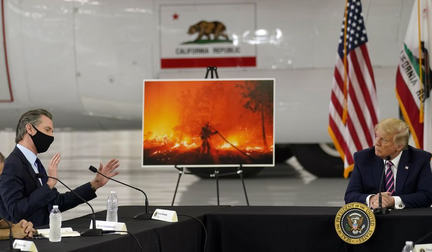President Donald Trump listens as California Gov. Gavin Newsom speaks during a briefing at Sacramento McClellan Airport, in McClellan Park, Calif., Monday, Sept. 14, 2020, on the western wildfires. (AP Photo/Andrew Harnik)