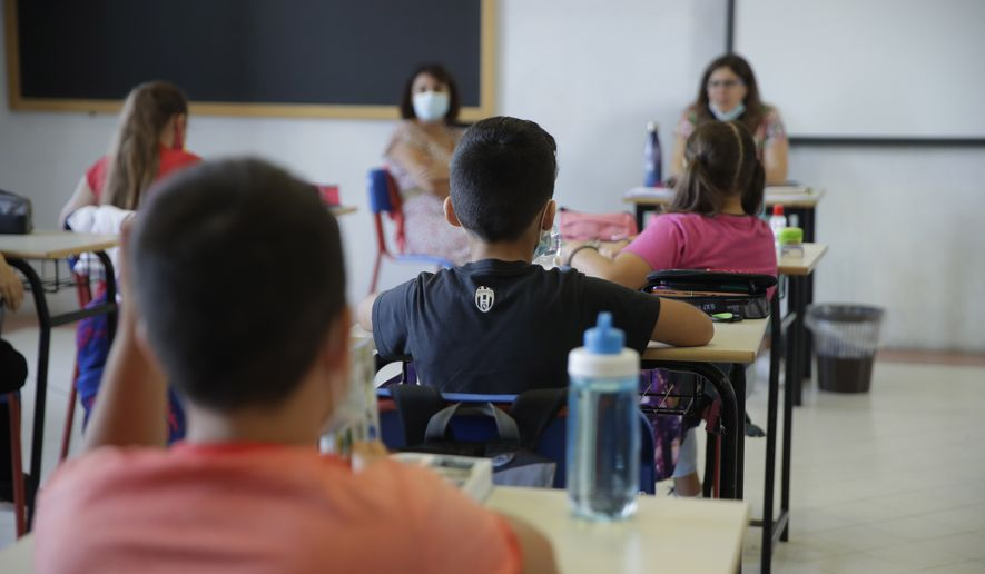 Students sit in their classroom at the San Biagio primary school in Codogno, Italy, Monday, Sept. 14, 2020. The morning bell Monday marks the first entrance to the classroom for the children of Codogno since Feb. 21,  when panicked parents were sent to pick up their children after the northern Italian town gained notoriety as the first in the West to record local transmission of the coronavirus. (AP Photo/Luca Bruno)