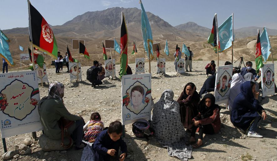 Families gather at the graves of their relatives, adorned with their pictures, on the outskirts of Kabul, Afghanistan, Monday, Sept 14, 2020. Scores of friends and families of students who were killed in local conflicts are gathering in a cemetery to call for a permanent countrywide ceasefire from the parties to the intra-Afghan peace conference taking place in Doha, Qatar. (AP Photo/Rahmat Gul)
