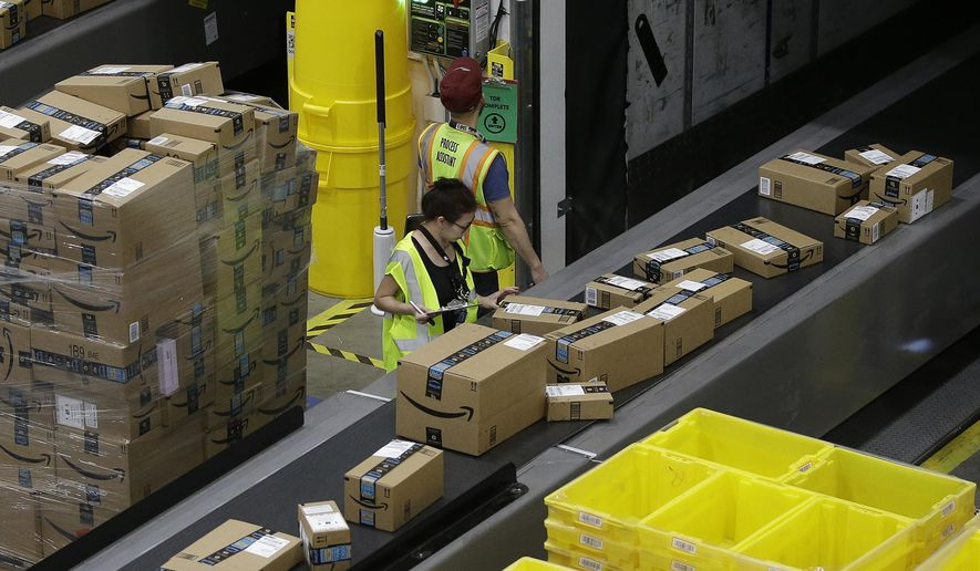 FILE - In this Feb. 9, 2018, file photo packages move down a conveyor system were they are directed to the proper shipping area at the new Amazon Fulfillment Center in Sacramento, Calif. Amazon said Monday, Sept. 14, 2020, that it will be hiring another 100,000 people to keep up with a surge of online orders. The company said the new hires will help pack, ship or sort orders, working in part-time and full-time roles. Amazon said the jobs are not related to its typical holiday hiring.  (AP Photo/Rich Pedroncelli, File)