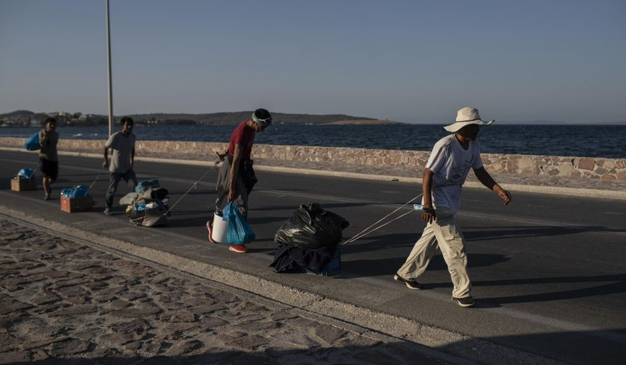 Migrants pull their belongings as they walk on a road near Mytilene town, on the northeastern island of Lesbos, Greece, Monday, Sept. 14, 2020. Greece's prime minister demanded Sunday that the European Union take a greater responsibility for managing migration into the bloc, as Greek authorities promised that 12,000 migrants and asylum-seekers left homeless after fire gutted an overcrowded camp would be moved shortly to a new tent city. (AP Photo/Petros Giannakouris)