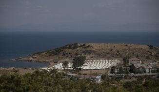 A general view of the temporary camp for refugees and migrants near Mytilene town, on the northeastern island of Lesbos, Greece, Sunday Sept. 13, 2020. Greek authorities have been scrambling to find a way to house more than 12,000 people left in need of emergency shelter on the island after the fires deliberately set on Tuesday and Wednesday night gutted the Moria refugee camp. (AP Photo/Petros Giannakouris)