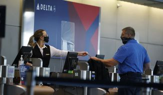 FILE - In this July 22, 2020 photo, a ticketing agent for Delta Airlines hands a boarding pass to a passenger as he checks in for a flight in the main terminal of Denver International Airport in Denver. Delta Air Lines will use its frequent flyer program to back up $6.5 billion in funding as the pandemic continues to buffet air travel. (AP Photo/David Zalubowski, File)