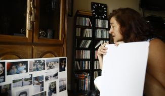 Christina Ihlenfeldt of Clinton Township, Mich., looks at old photos of her late husband in her home on Tuesday, Aug. 25, 2020. She became widowed, unemployed and lost $30,000 from a scam in one week. Heartbroken and vulnerable, the scam group using the name Geek Squad conned her into wiring them money to fix her computer. Her late husband, Robert Ihlenfeldt passed away on Friday, Aug. 7, 2020. (Rodney Coleman-Robinson/Detroit Free Press via AP)