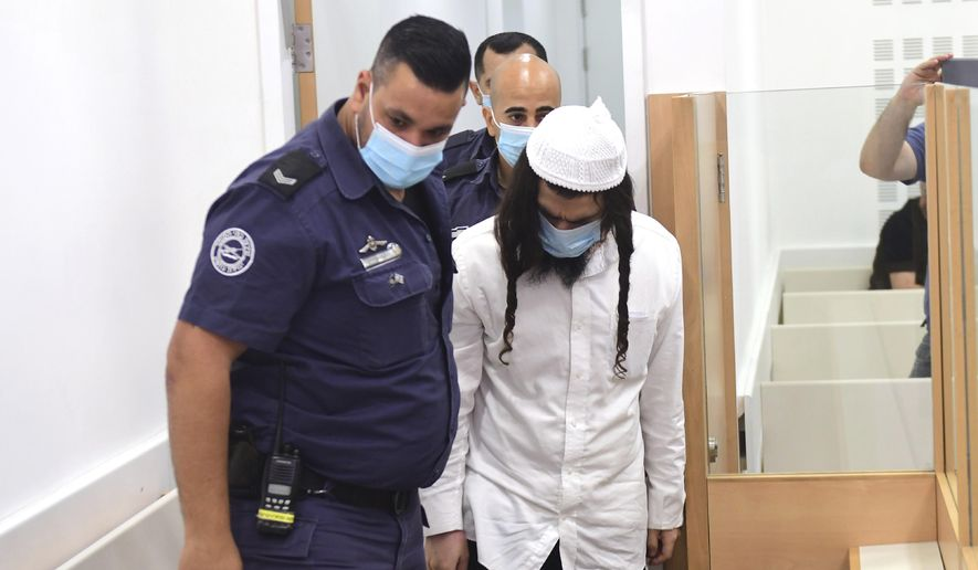 In this May 18, 2020, file photo, Israeli Jewish extremist Amiram Ben-Uliel arrives at a district court for a verdict in Lod, Israel. On Monday, Sept. 14, 2020, an Israeli court handed down three life sentences to Ben-Uliel convicted in a 2015 arson attack that killed a Palestinian toddler and his parents. The Lod District Court found the Jewish settler guilty of murder in May for the killing of 18-month-old Ali Dawabsheh by firebombing his home in the West Bank village of Duma. (Avshalom Sassoni/Pool Photo via AP, File)