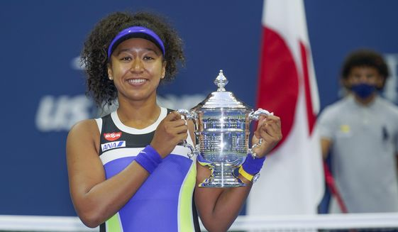 In this Sept. 12, 2020, file photo, Naomi Osaka, of Japan, holds up the championship trophy after defeating Victoria Azarenka, of Belarus, in the women's singles final of the US Open tennis championships, in New York. Osaka's victory in the U.S. Open helped raised the issue of racial injustice in the United States. Before each of her matches, she wore a mask with the names of seven Black Americans who died as victims of violence. The daughter of a Japanese mother and Haitian father, she has become a leader of the Black Lives Matter movement. (AP Photo/Seth Wenig)  **FILE**