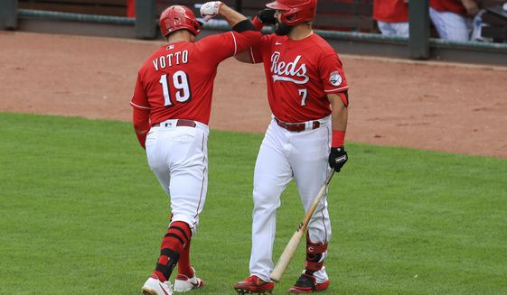 Cincinnati Reds' Joey Votto, left, reacts with Eugenio Suarez, right, after hitting a solo home run in the fourth inning during a baseball game against the Pittsburgh Pirates in Cincinnati, Monday, Sept. 14, 2020. (AP Photo/Aaron Doster)